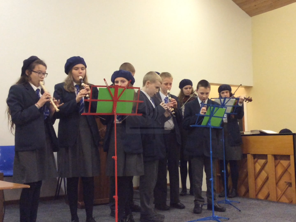 Some High School students perform an instrumental carol